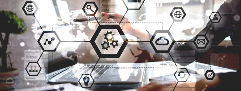 Ein Mitarbeiter des Unternehmens e-velopment zeigt mit einem Stift auf den Bildschirm eines ERP-System und erklärt e-commerce